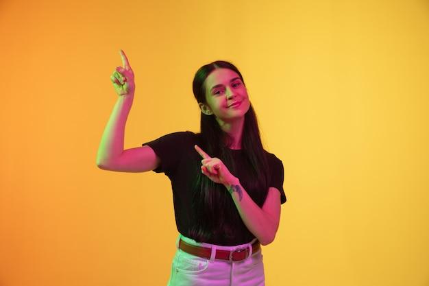Porträt der kaukasischen jungen frau lokalisiert auf studiohintergrund im neonlicht.