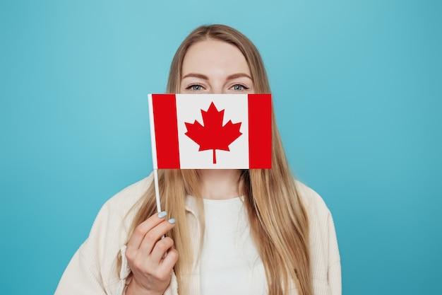 Porträt der kaukasischen studentin, die ihr gesicht mit kleiner kanadischer flagge bedeckt