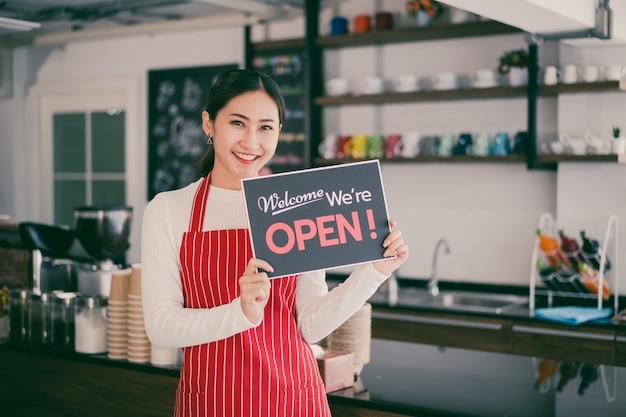 Porträt der kellnerin der frau, die an ihrem kaffeehaus-tor mit offenem schild steht