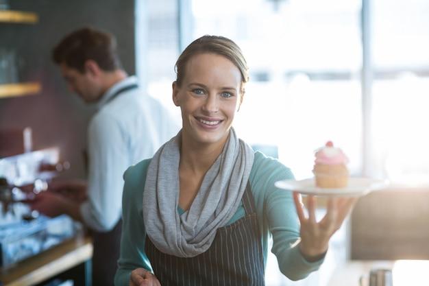 Porträt der kellnerin, die einen teller cupcake hält