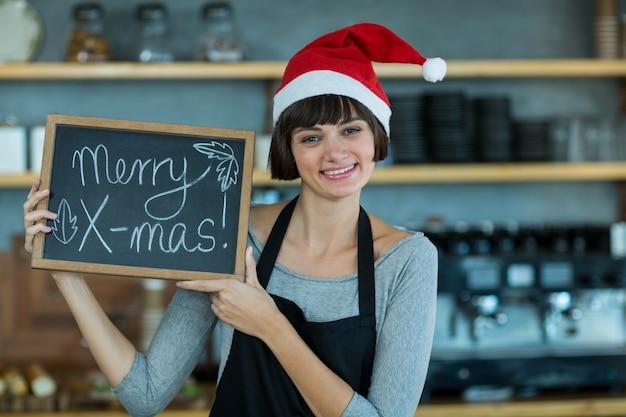 Porträt der kellnerin, die schiefer mit fröhlichem weihnachtsschild zeigt
