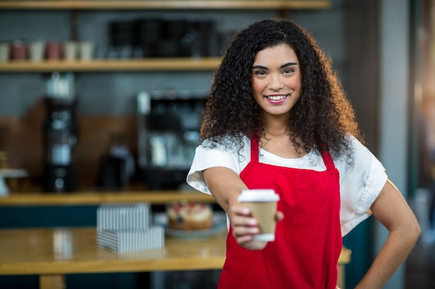 Porträt der kellnerin mit einwegbecher kaffee