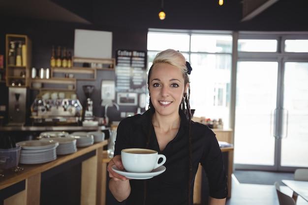 Porträt der kellnerin stehend mit tasse kaffee