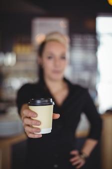 Porträt der kellnerin stehend mit wegwerfkaffeetasse