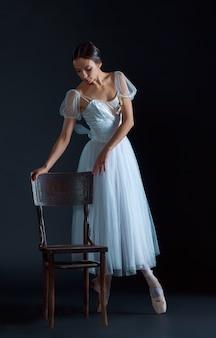 Porträt der klassischen ballerina im weißen kleid auf schwarz
