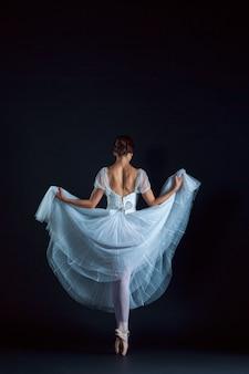 Porträt der klassischen ballerina im weißen kleid auf schwarzer wand