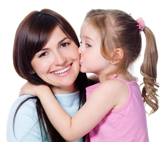 Porträt der kleinen tochter, die ihre schöne glückliche mutter küsst - lokalisiert auf weiß