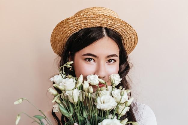 Porträt der koreanischen dame, die blumen hält und kamera betrachtet. studioaufnahme der asiatischen frau im strohhut mit weißen eustomas.
