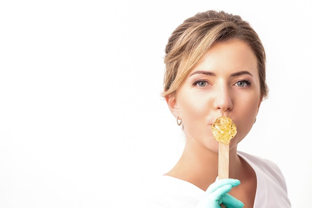 Porträt der kosmetikerin hält einen holzstab mit einem wachs, das ihre lippen auf weiß bedeckt