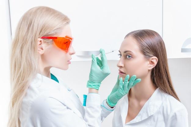 Porträt der kosmetikerin und des patienten. der arzt injiziert botox. hautverjüngungs- und lifting-konzept. gemischte medien