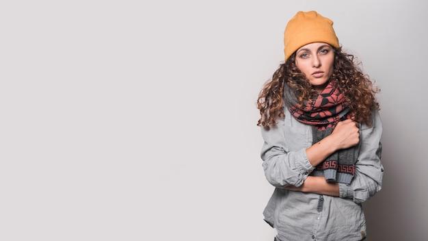 Porträt der kranken frau mit woolen schal um ihren hals und wolligen hut