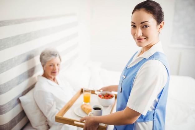 Porträt der krankenschwester der älteren frau im schlafzimmer frühstück gebend