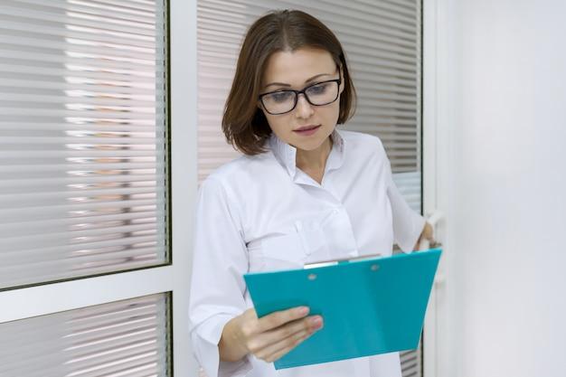 Porträt der krankenschwester der erwachsenen frau, frau mit dem klemmbrett, arbeitend im krankenhaus.