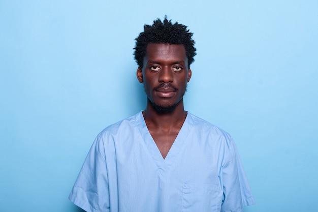 Porträt der krankenschwester des schwarzen mannes, die über blauem hintergrund steht