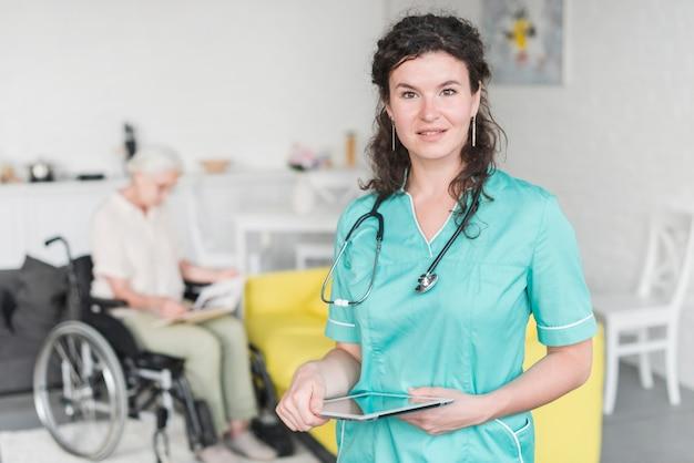 Porträt der krankenschwester die digitale tablette halten, die vor älterem weiblichem patienten auf rollstuhl steht