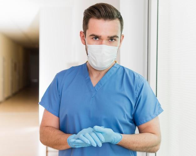 Porträt der krankenschwester, die maske und handschuhe trägt