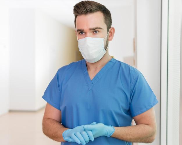 Porträt der krankenschwester, die medizinische maske und handschuhe trägt