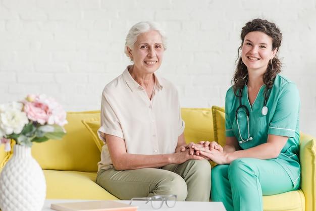 Porträt der krankenschwester sitzend mit älterem weiblichem patienten auf sofa