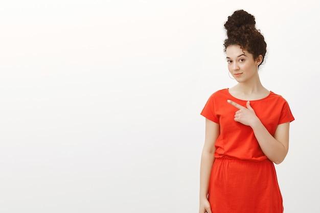 Porträt der kreativen charmanten studentin mit den lockigen haaren im trendigen roten kleid mit brötchenfrisur