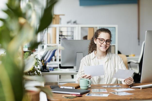 Porträt der kreativen jungen frau, die an der kamera lächelt, während sie fotografien im verlagsbüro, kopierraum überprüft