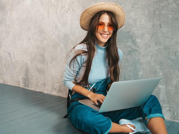 Porträt der kreativen jungen lächelnden frau in der sonnenbrille. schönes mädchen, das auf dem boden nahe grauer wand sitzt.