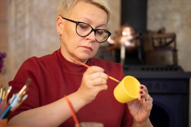 Porträt der künstlerin, die auf gelbem tontopf im kunstheimstudio malt