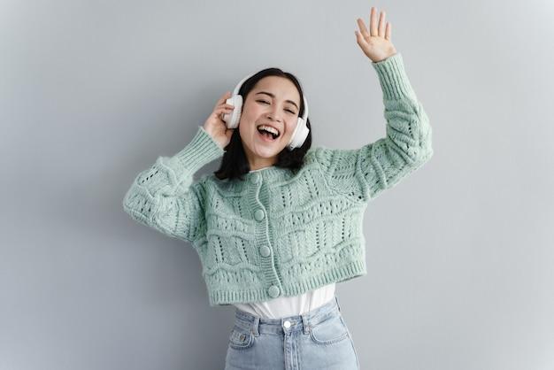Porträt der kurzhaarigen jungen frau, die mit kopfhörern tanzt