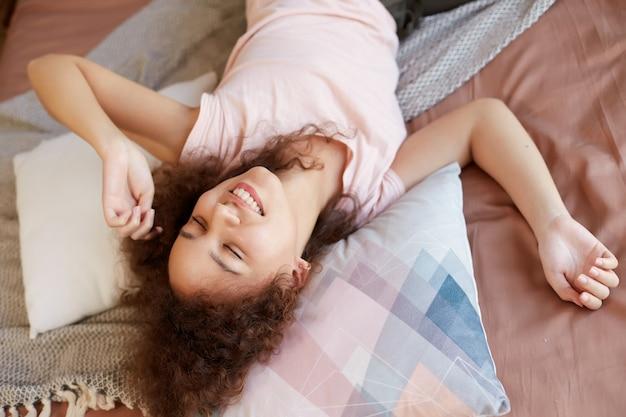 Porträt der lachenden dunkelhäutigen jungen frau, die auf dem bett liegt, genießt den sonnigen tag zu hause, breit lächelnd und sieht glücklich aus.