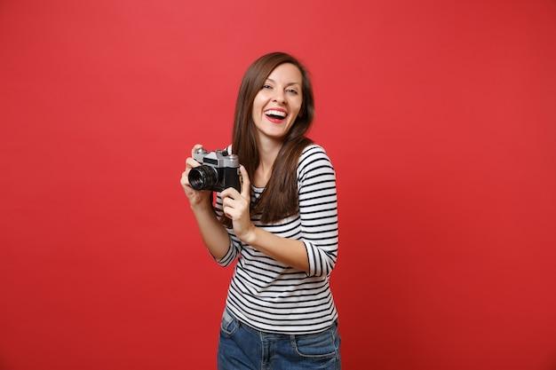 Porträt der lachenden jungen frau in der zufälligen gestreiften kleidung, die retro- weinlesefotokamera lokalisiert auf hellem rotem wandhintergrund hält. menschen aufrichtige emotionen, lifestyle-konzept. kopieren sie platz.