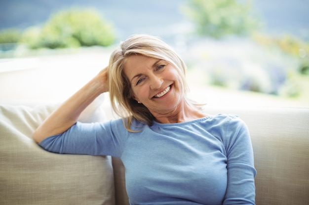 Porträt der lächelnden älteren frau, die auf sofa im wohnzimmer sitzt