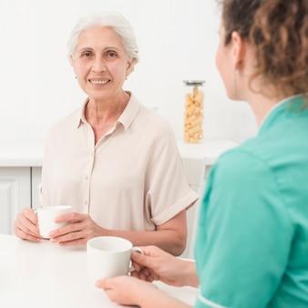 Porträt der lächelnden älteren frau, die mit der krankenschwester hält kaffeetasse sitzt