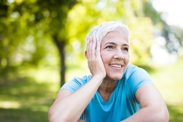 Porträt der lächelnden älteren frau, die nach dem trainieren sich entspannt