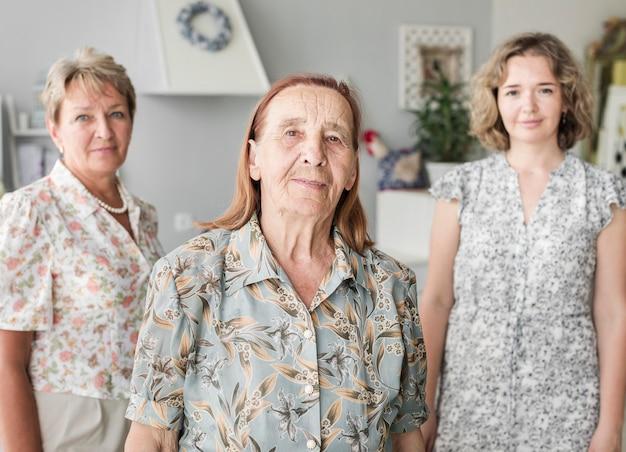 Porträt der lächelnden älteren frau, die verwelkt ihre tochter und großartige tochter steht