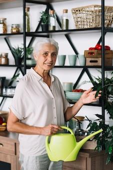 Porträt der lächelnden älteren frau, die zu hause anlage der bewässerungsdose berührt hält