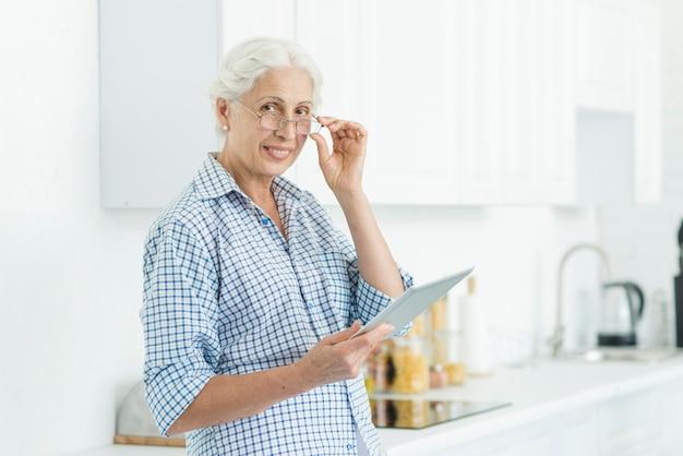 Porträt der lächelnden älteren frau, welche die digitale tablette steht in der küche hält