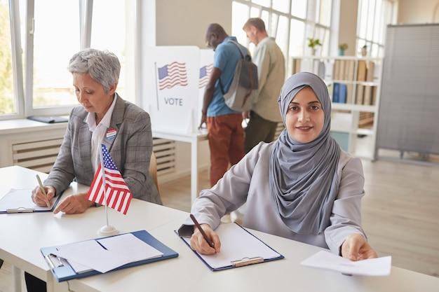 Porträt der lächelnden arabischen frau, die dem wähler papiere während der arbeit am wahllokal übergibt, kopieren raum