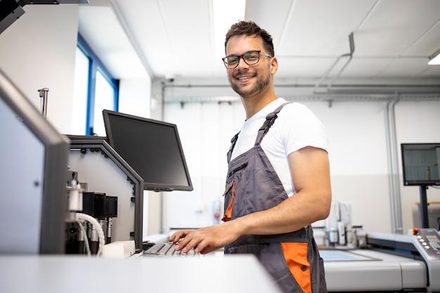 Porträt der lächelnden arbeitskraft, die durch industrielle produktionsmaschine steht.