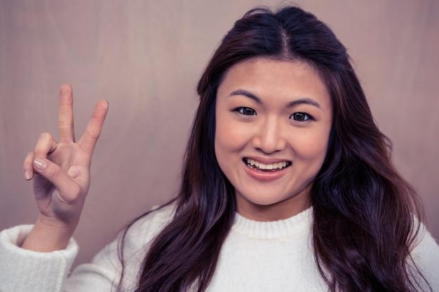 Porträt der lächelnden asiatin friedenszeichen machend