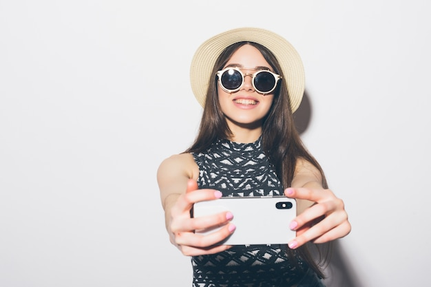 Porträt der lächelnden attraktiven frau im hut stehend und ein selfie isoliert