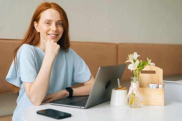 Porträt der lächelnden attraktiven jungen frau, die am tisch mit laptop und telefon im café mit warmem tageslicht sitzt und kamera betrachtet. hübsche kaukasische dame der rothaarigen entfernt, die arbeitet oder studiert.