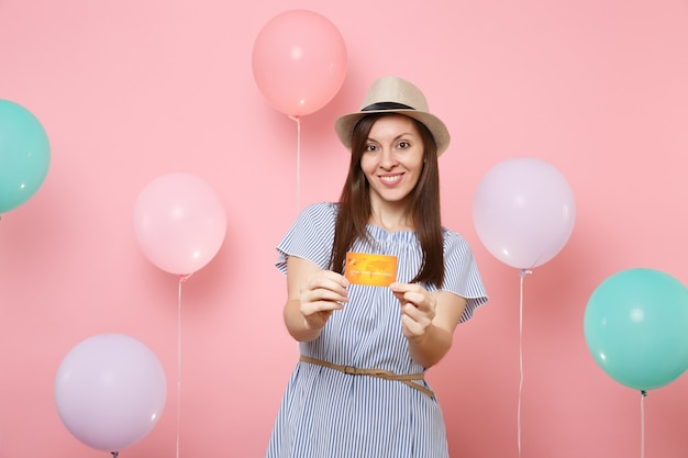 Porträt der lächelnden attraktiven jungen frau in strohsommerhut und blauem kleid, die kreditkarte auf pastellrosa hintergrund mit bunten luftballons halten. geburtstagsfeier-partyleute aufrichtige gefühle.