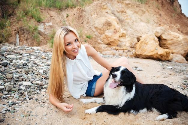 Porträt der lächelnden attraktiven jungen frau mit hund am strand