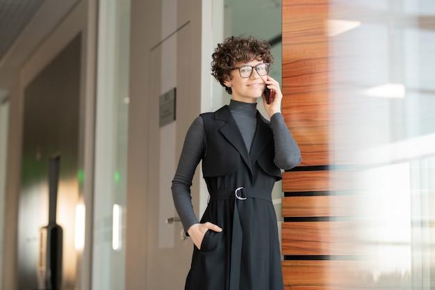 Porträt der lächelnden attraktiven jungen geschäftsfrau in den brillen und im schwarzen kleid, die im korridor stehen und mit dem kunden am telefon sprechen