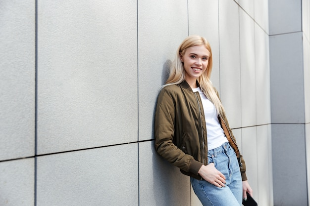 Porträt der lächelnden blonden frau gegen graue wand