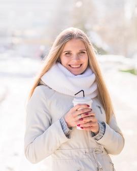 Porträt der lächelnden blonden jungen frau, die wegwerfkaffeetasse hält