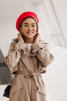 Porträt der lächelnden braunäugigen asiatischen frau in der stilvollen brille, der roten baskenmütze im französischen stil und dem beigen trenchcoat, der vorne gegen fenster schaut