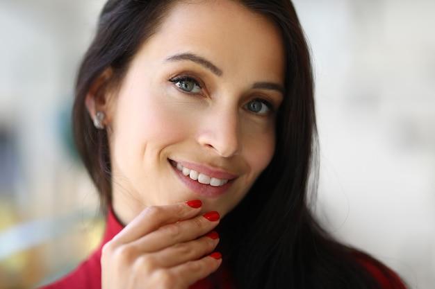 Porträt der lächelnden brünetten frau mit roter maniküre
