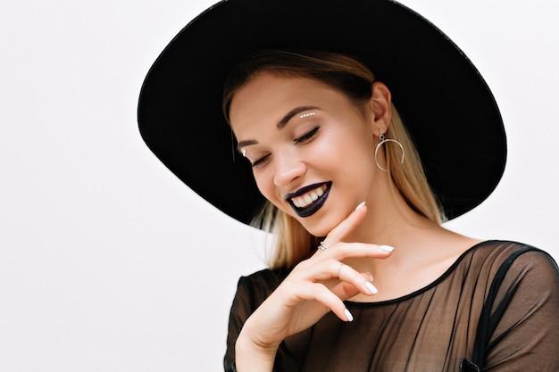 Porträt der lächelnden charmanten frau mit schwarzem lippenstift und schwarzem hut