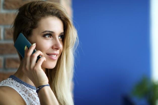 Porträt der lächelnden charmanten jungen frau, die auf handy spricht und wegschaut. blonde dame, die modernes smartphone hält. kopieren sie den speicherplatz auf der rechten seite. technologie und schönes gesprächskonzept
