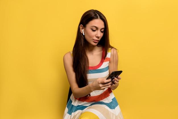 Porträt der lächelnden charmanten stilvollen jungen frau, die auf smartphone in kopfhörern arbeitet